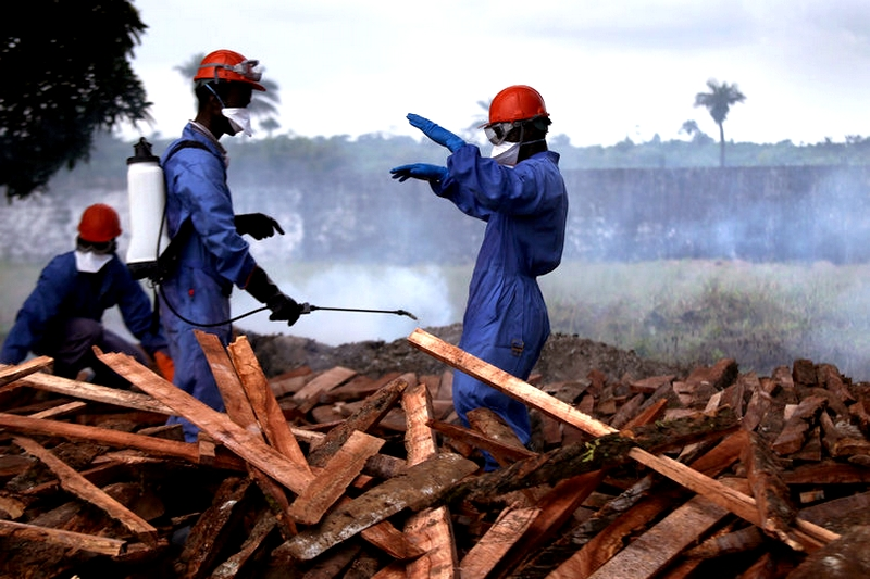 Burial teams from the Liberian Ministry of Health disinfect themselves before burning the bodies of Ebola victims in Marshall, Liberia. Source: Two new cases of Ebola reported in Democratic Republic of Congo, August 24, 2014