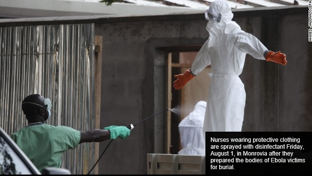 Nurses wearing protective clothing are sprayed with disinfectant Friday, August 1, in Monrovia after they prepared the bodies of Ebola victims for burial